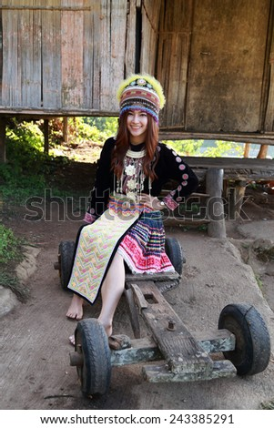 Traditionally dressed Mhong hill tribe woman at the wooden cottage - stock photo