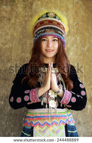 Traditionally dressed Mhong hill tribe woman pay respect at the wooden cottage - stock photo