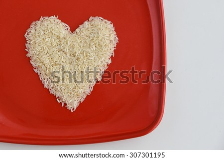 Traditionally Indian basmati Rice in heart shape in a red plate, isolated over white with copy space.Symbol of love or LUV. White rice or biriyani rice Kerala India - stock photo