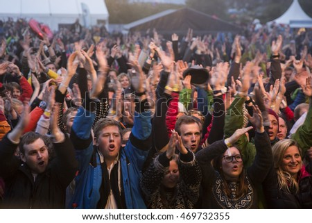 Traena, Norway - July 08, 2016: audience cheering at concert of Norwegian folk and rock band Violet Road at Traenafestival, music festival taking place on the small island of Traena in Norway