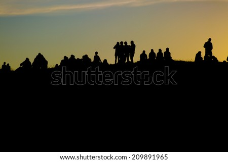 Traena, Norway-July 11 2014: people watching the concert of the Swedish pop-techno band Den svenska bjornstammen from the top of the hill at the Traenafestival, music festival held on Traena island