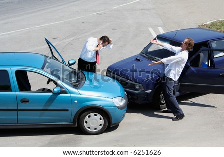 Traffic accident - one driver on the mobile phone, second expressing anger - stock photo