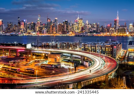 Traffic and light trails on The Helix, a highway loop at the entrance in Lincoln Tunnel. The New York skyline shines in the background. - stock photo