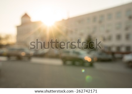 Traffic at sunset, defocused image of a road lit with warm light of setting sun - stock photo