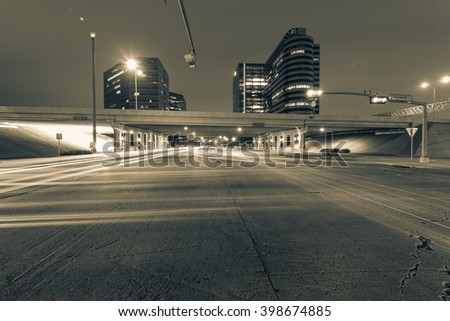 Traffic at the intersection of Sam Houston Parkway express with light trails from vehicle headlight motion. Transportation urban and motion concept. Houston, Texas. Black and White view - stock photo