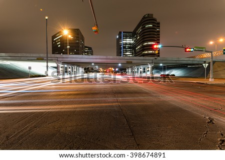Traffic at the intersection of Sam Houston Parkway express with light trails from vehicle headlight motion. Transportation urban and motion concept. Houston, Texas. - stock photo