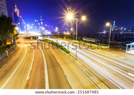 Traffic blur motion trails in modern city street at night - stock photo