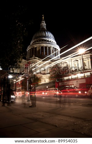 Traffic by St Paul's Cathedral at night, London. Blurred motion of passers-by and traffic. - stock photo