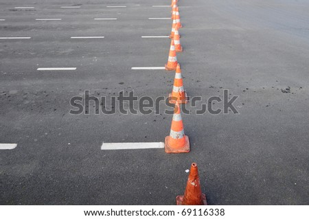 Traffic cones in empty parking space (asphalt with withe lines) - stock photo