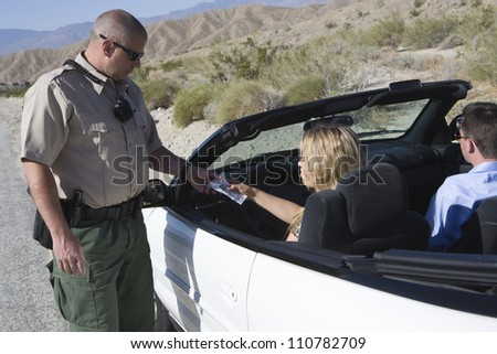 Traffic cop checking woman's license - stock photo