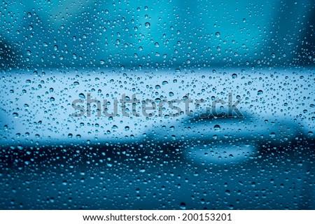 Traffic detail in rain. Low DOF of a car door handle through the rain drops on a window. - stock photo
