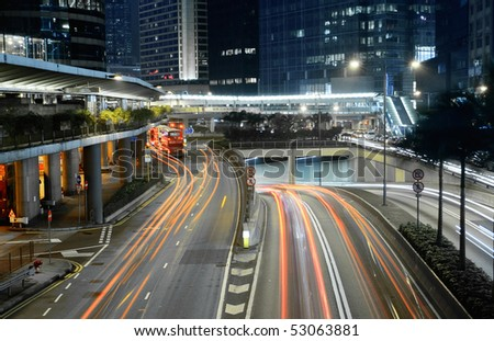 Traffic in city with cars motion blurred light and office building in night. - stock photo