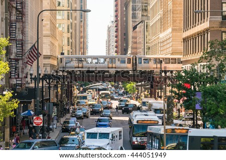 Traffic in downtown Chicago with people, train, car and bus - stock photo