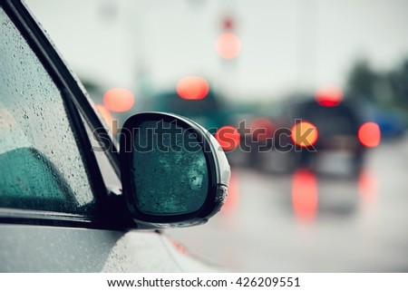 Traffic in heavy rain in the city. Raindrop on the mirror of the car. - stock photo