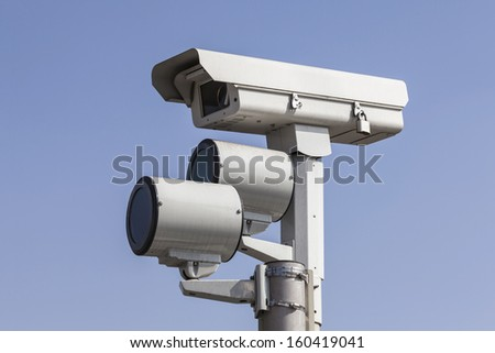 Traffic intersection signal surveillance camera with lights. - stock photo