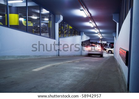 Traffic jam in parking garage, motion blur from moving car. Neon light in bright industrial building.