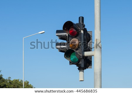 traffic light against a clear blue sky, with lamp post in background - stock photo