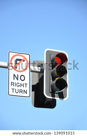 Traffic light and NO RIGHT TURN sign on blue background - stock photo
