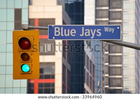 traffic light and street sign with office building in background - stock photo