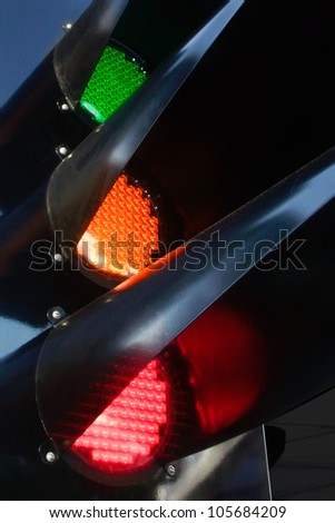 traffic light glowing of the different colors of green, red and yellow black steel mechanism - stock photo