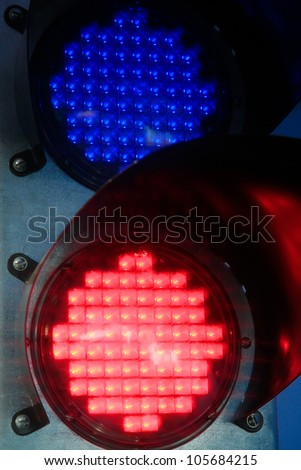 traffic light glowing of the different colors of red and blue in black steel mechanism - stock photo