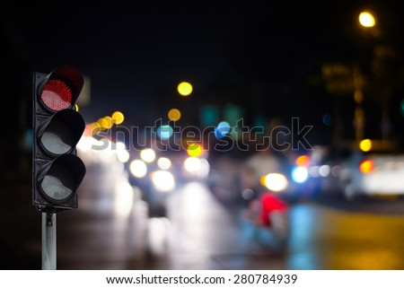 Traffic light on the road during the night - stock photo