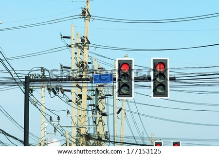 Traffic light poles and power poles with tangled wires on the traffic intersection -Bangkok, Thailand. - stock photo