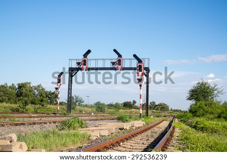 Traffic light signal and line of railway tracks crossing in country of Thailand with white cloud and blue sky background - stock photo