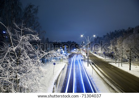 Traffic light stream in city at night in winter - stock photo