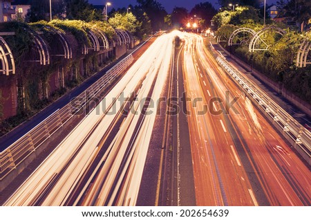 traffic light trails in green urban area - stock photo