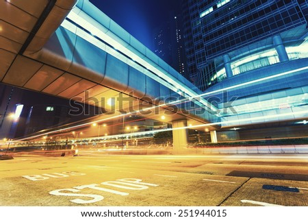 traffic light trails in modern city at night - stock photo