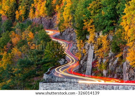 Traffic light trails on Hawk's Nest winding road (route 97) in Upstate New York, on an autumn evening. - stock photo