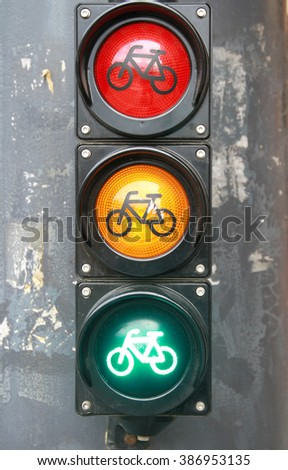 Traffic light with bike sign for cyclists close up.  Red yellow green  light for bicycle lane.  Red orange green colored traffic lights as a background  - stock photo