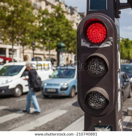 traffic light with pedestrian and traffic in the blurred background - stock photo