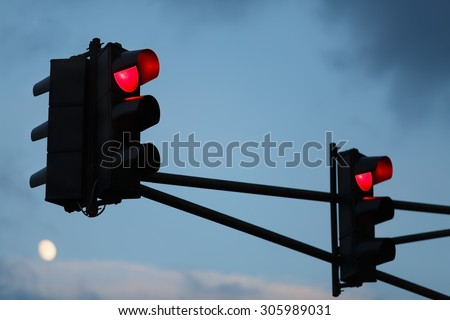 Traffic light with red light against the evening sky. Shallow depth of field. Selective focus. - stock photo