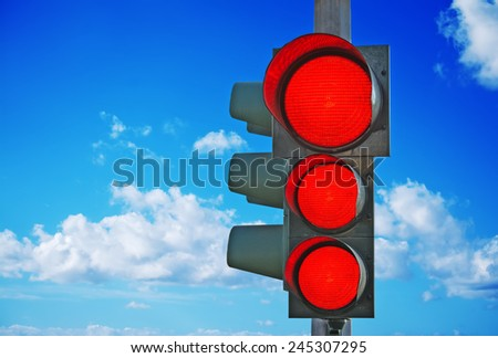 traffic light with three red lights on under a blue sky