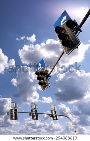 Traffic lights against a vibrant blue sky with clouds. - stock photo