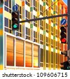 Traffic lights against colorful building with sunset reflection in the window. Tel-Aviv, Israel - stock photo