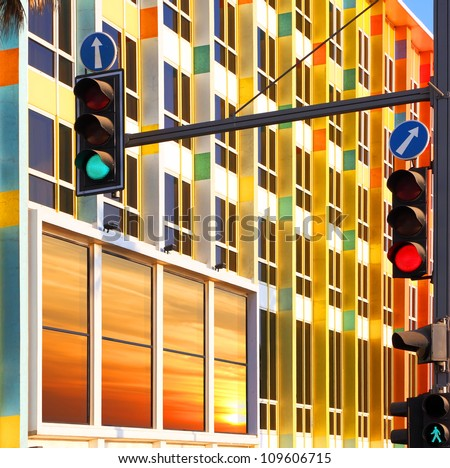 Traffic lights against colorful building with sunset reflection in the window. Tel-Aviv, Israel