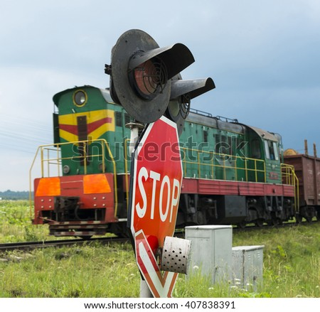 Traffic lights and signs at the railroad crossing and the approaching freight train (Ukraine). - stock photo