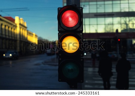 Traffic lights at an intersection at a pedestrian crossing on a winter evening - stock photo