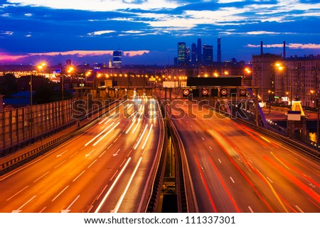 traffic lights at the road (highway) in dusk at sunset (sunrise). moscow night city landscape