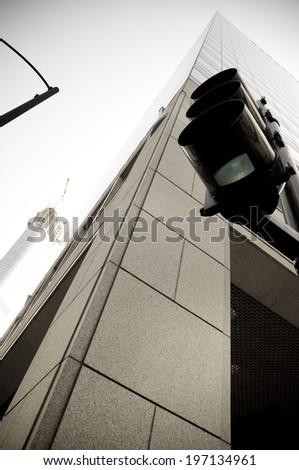 Traffic lights beside a tall skyscraper during the day. - stock photo