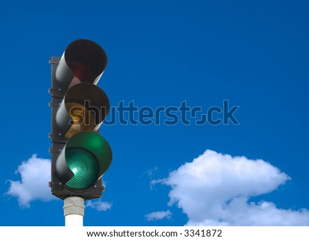 Traffic lights - green light is on - in front of blue sky - stock photo
