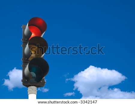 Traffic lights - red light is on - in front of blue sky - stock photo