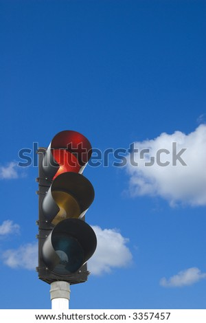 Traffic lights - red light is on in front of blue sky - stock photo