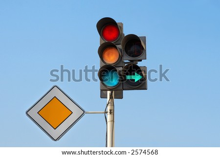 "traffic lights (red + yellow + green) with additional section ""right turn"" and sign ""main road"" - stock photo"