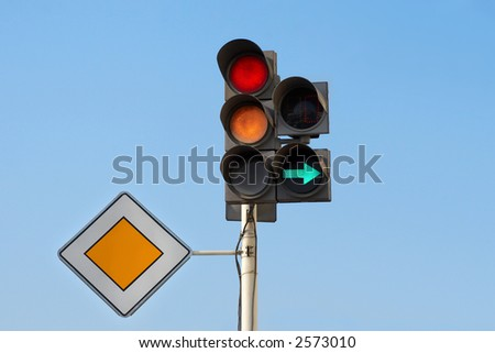 """traffic lights (red & yellow) with additional section """"right turn"""" and sign """"main road"""" - stock photo"""