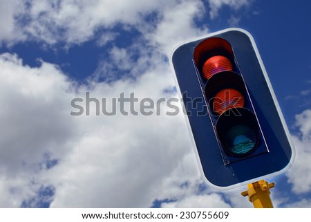 Traffic lights with red, yellow and green lights against the skies and clouds - stock photo