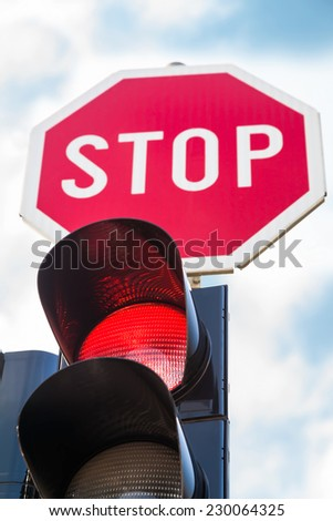 Traffic lights with the red light lit and stop sign - stock photo